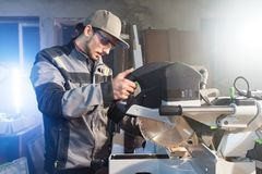 Young brunette man wearing a cap in a gray jacket by profession a carpenter cuts wooden boards with a circular saw on a. Workbench table in a workshop stock photo