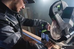 Young brunette man wearing a cap in a gray jacket by profession a carpenter cuts wooden boards with a circular saw on a. Workbench table in a workshop royalty free stock photography