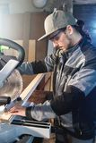 Young brunette man wearing a cap in a gray jacket by profession a carpenter cuts wooden boards with a circular saw on a. Workbench table in a workshop royalty free stock photo