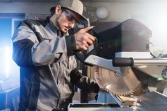 Young brunette man wearing a cap in a gray jacket by profession a carpenter cuts wooden boards with a circular saw on a. Workbench table in a workshop royalty free stock photos