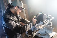 Young brunette man wearing a cap in a gray jacket by profession a carpenter cuts wooden boards with a circular saw on a. Workbench table in a workshop stock images