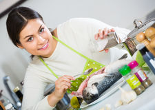 Young brunette marinating rainbow trout indoors. Smiling woman in white sweater marinating rainbow trout indoors stock image