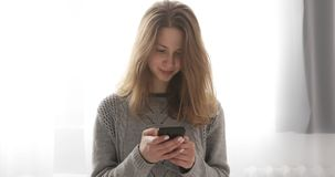Young brunette model in grey sweater typing message on mobile phone standing near the window. A smiling girl with long hair with smartphone stock footage