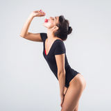 Young brunette model with lollipop studio shot on white background, not isolated Stock Photography