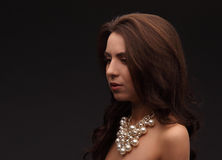 Young brunette model over dark background naked with necklace looking somewhere Stock Images