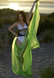 Young brunette model posing in design  bikini and holding green floating beach cover up on sunset time Stock Photo