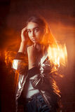 Young brunette model in shiny silver jacket and blue jeans. Mixe Stock Photography