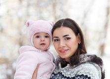 Young brunette mother with her daughter outdoors. Winter Royalty Free Stock Images