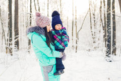 Young brunette mother with her daughter outdoors. Winter time Royalty Free Stock Photos