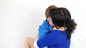 Young brunette mother hugs her son on a white sofa. The concept of a happy family stock video