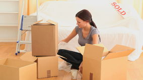 Young brunette packing her cups stock video footage