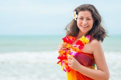 Young brunette in pareo and flower lei against the sea Royalty Free Stock Image