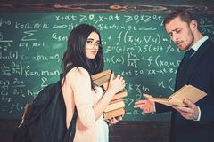 Young brunette in pink cardigan wearing glasses holding heap of books while professor is reading. Teacher and college. Girl standing in front of green board stock photography