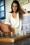 Young brunette playing chess Stock Photography