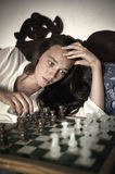 Young brunette playing chess Royalty Free Stock Photos