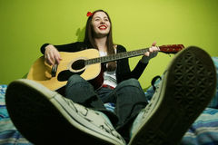 Young brunette playing guitar on bed Royalty Free Stock Photography