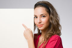 Young brunette pointing at banner. Royalty Free Stock Photography