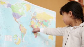 Young brunette pointing a world map stock video footage
