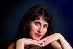 Young brunette portrait shot in studio on a dark background Stock Image