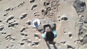 Young brunette pretty woman controls piloting drone copter using console holding phone at ocean beach. Smart girl. Young woman controls piloting drone copter stock video footage