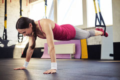 Young brunette is pushing on the trx Stock Photography