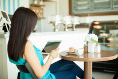 Young brunette reading in a cafe Royalty Free Stock Photo