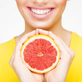 Young brunette with red grapefruit in her hand Royalty Free Stock Photography