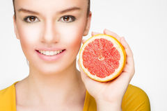 Young brunette with red grapefruit in her hand Stock Photography