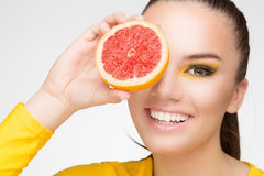 Young brunette with red grapefruit in her hand Royalty Free Stock Image