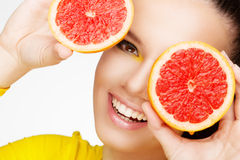 Young brunette with red grapefruit in her hand Stock Photos