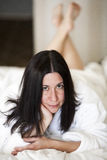 Young brunette relaxing in a white bathrobe 1. A young woman lays on a bed, relaxing in her plush bathrobe Stock Photo
