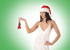 A young brunette in a Santa hat is holding a bell Stock Photo