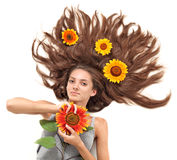 Young brunette with scattered hairs and sunflower Stock Photo
