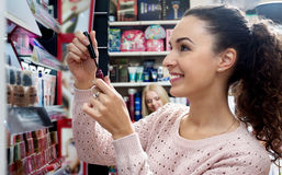 Young brunette selecting lip gloss Royalty Free Stock Images