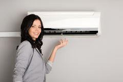 Young brunette showing the air conditioner Royalty Free Stock Images