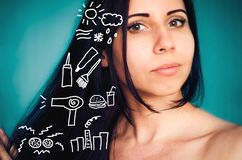 Young brunette shows different destroying factors for hair stock image