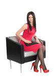 Young brunette sitting on a chair Stock Photo
