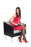 Young brunette sitting on a chair Royalty Free Stock Photo