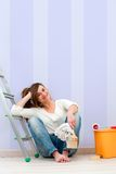 Young brunette sitting on floor after painting. Stock Photography