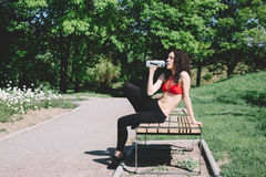 Young brunette sitting in green park on a bench Stock Image