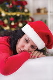 Young brunette sitting next Christmas tree looking lonely Royalty Free Stock Images