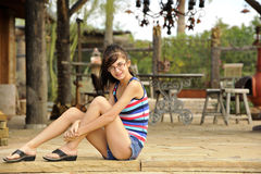 Young Brunette Sitting on Stone Patio Stock Photo