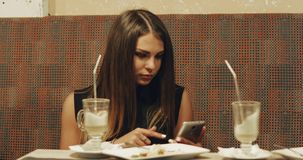 Young brunette sitting at table and drinking latte at bar. stock video