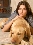 A young brunette with a sleeping dog Stock Images