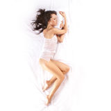 A young brunette is sleeping on white silk Stock Image