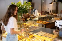 Young brunette smile woman near modern display of bakery with different kinds of cookie and buns and choose and make stock image