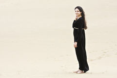 Young brunette standing on sand Royalty Free Stock Images