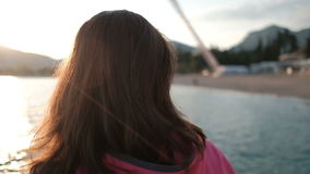 Young brunette stands on the coast of lake looking on the sunset. stock footage