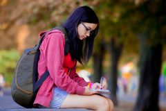 Young brunette student girl with backpack. At city outdoor Stock Photos