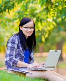 Young brunette student girl with laptop computer. Studying on green grass in summertime Stock Photography